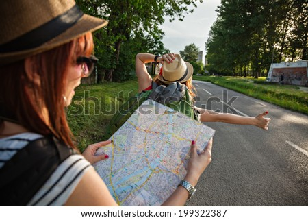 Two Young Tourist Girl Hitchhiking On The Road - stock photo