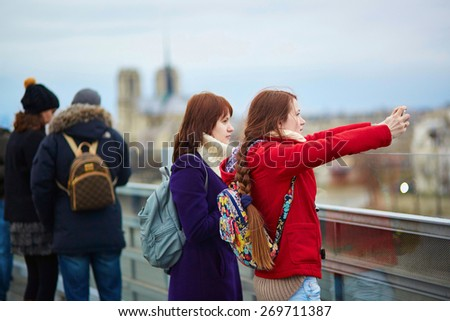 Two young tourist in Paris, making a photo using mobile phone from the Arab World Institute observation deck - stock photo