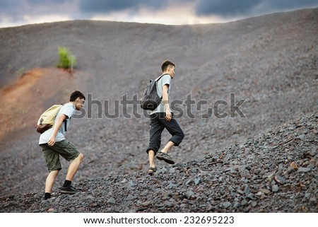 Two young tourist men walks on stones and rock slope - stock photo