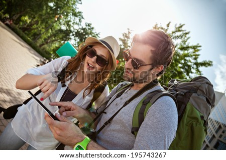 Two Young Tourists Sightseeing City Using Digital Tablet - stock photo
