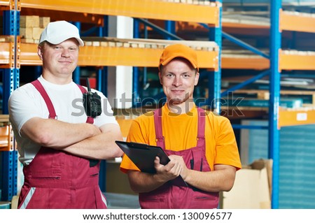 two young warehouse workers men in uniform in front of warehouse rack arrangement stillages - stock photo