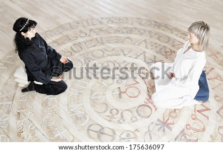 Two young woman black and white dressed doing yoga - stock photo