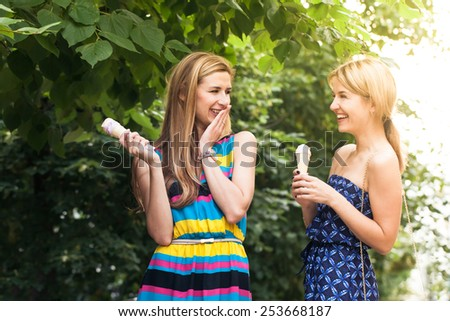 Two young woman chatting and eating ice cream - stock photo