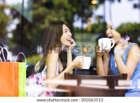 two young woman chatting in a coffee shop - stock photo