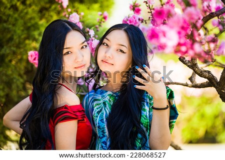 Two young woman in the rays of the spring sun. - stock photo