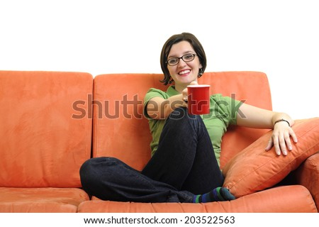 two young woman isolated on white with cup off coffee talking and chating isolated on whtie on orange sofa - stock photo
