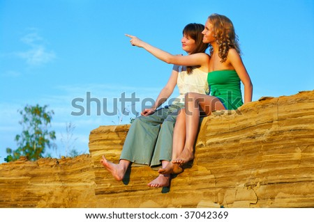 two young woman looking at sunset sitting on the edge of mountain - stock photo