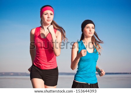 two young woman running on the beach - stock photo