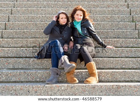 Two young woman sitting on steps on an autumn afternoon - stock photo