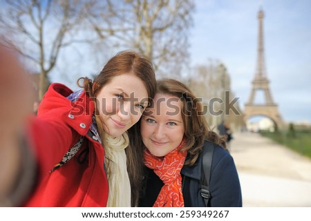 Two young woman taking a self portrait (selfie) near the Eiffel tower - stock photo