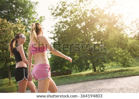 Two young woman walking at the park - stock photo