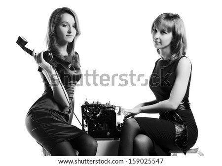 Two young woman with a vintage typewriter and retro phone - stock photo
