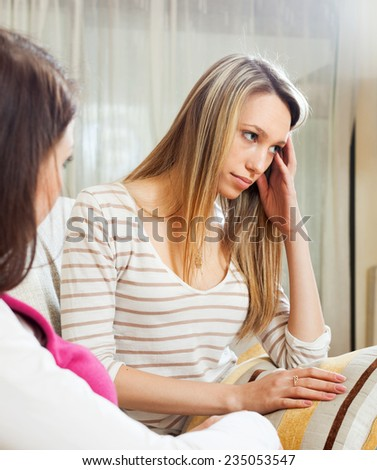Two young  women after quarrel in home - stock photo