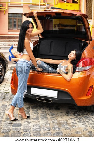 Two young women and a car, one is standing near a car and the second is located in the trunk - stock photo