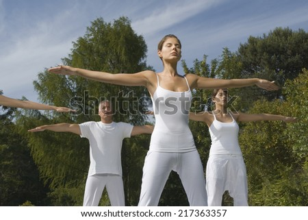 Two young women and a mature man exercising in a park - stock photo