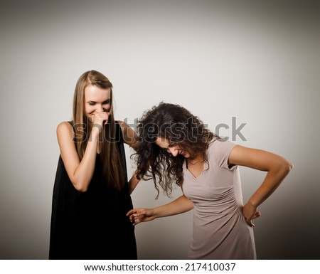 Two young women are having a joyful conversation. Interaction. Young women are doing something. - stock photo