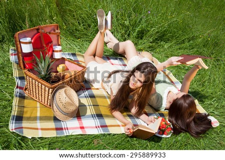 Two young women - best friend, enjoying summertime, having picnic, lying on grass and reading books. - stock photo