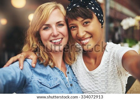 Two young women best friends sitting arm in arm with their faces close together smiling at the camera, multiethnic couple - stock photo