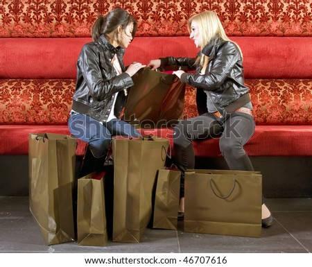 two young women checking out their purchases in a trendy lounge - stock photo