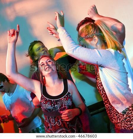 Two young women dancing in a busy nightclub - stock photo