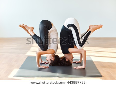 Two young women doing yoga asana crane pose. Bakasana - stock photo