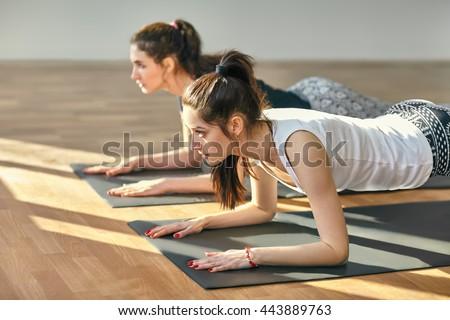 Two young women doing yoga asana Low Plank Pose. Ardha Phalakasana - stock photo