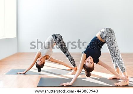 Two young women doing yoga asana revolved downward facing dog. Adho Mukha Svanasana - stock photo