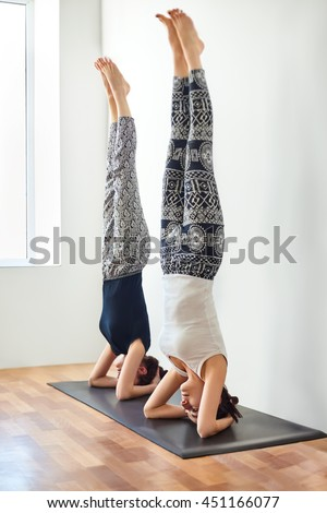 Two young women doing yoga asana  supported headstand. Salamba Sirsasana - stock photo