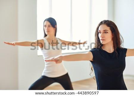 Two young women doing yoga asana Virabhadrasan. Warrior Pose - stock photo