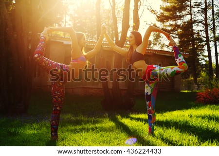 Two young women doing yoga outdoors in the evening - stock photo