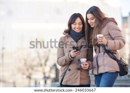 Two young women drinking coffee on the street - stock photo
