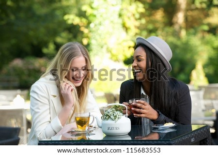 Two young women drinking tea and gossiping - stock photo