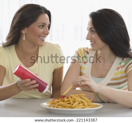 Two young women eating french fries - stock photo