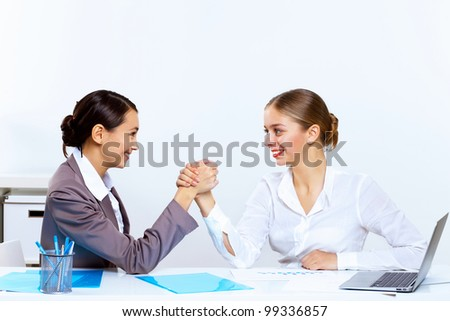 Two young women in business wear arm wrestling in office - stock photo