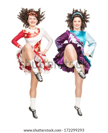Two young women in irish dance dress dancing isolated - stock photo