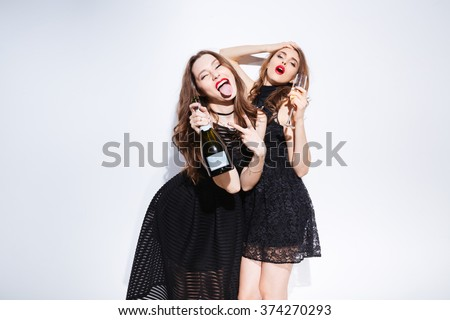 Two young women in night dress drinking champagne and showing tongue isolated on a white background  - stock photo