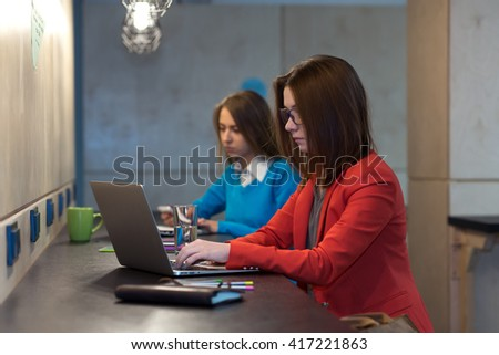 Two young Women in red and blue Jacket working on Laptop Computers at wooden Bar Counter one smiling another with serious Face Expression - stock photo