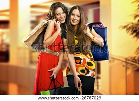 Two young women in shopping center - stock photo