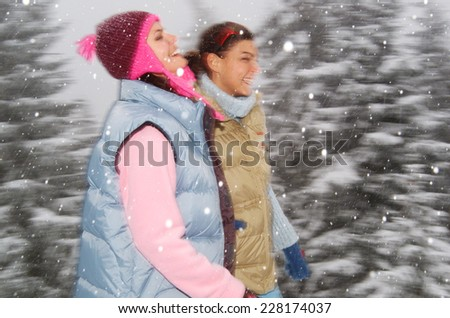 Two young women in winter landscape - stock photo