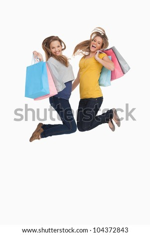 Two young women jumping with shopping bags against white background - stock photo