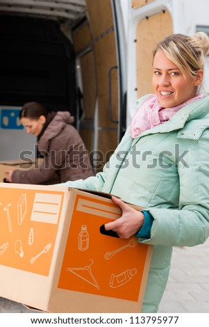 Two young women loading into a moving truck, they carry moving boxes - stock photo