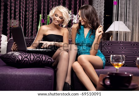 Two young women looking at notebook - stock photo