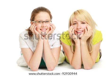Two young women lying on floor isolated on white background - stock photo