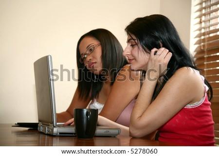 Two young women (middle eastern and chinese indonesian) with laptop in home. - stock photo