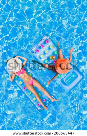 Two Young women on lilos at the swimming pool  - stock photo