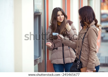 Two young women picking money from ATM - stock photo