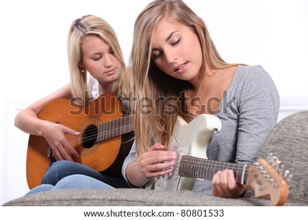 Two young women playing the guitar. - stock photo