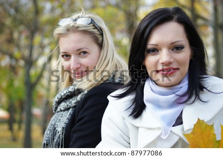 two young women posing in a park - stock photo