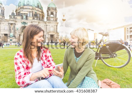 Two young women relaxing in Berlin with the Cathedral and Fernsehturm tv tower on background. They have a smart phone and they are looking each other smiling. Friendship and lifestyle concepts. - stock photo