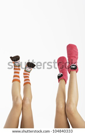 Two young women's legs up in the air wearing funny socks. - stock photo